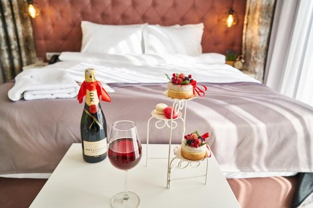 Hotelový pokoj, velká postel, v popředí na stolku připraveno pohoštění