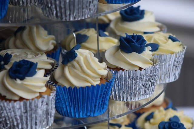 a blue topping on small cakes on a wedding table