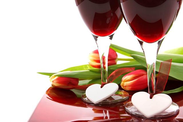 Dvě skleny s červeným vínem, s přiloženými srdíčky